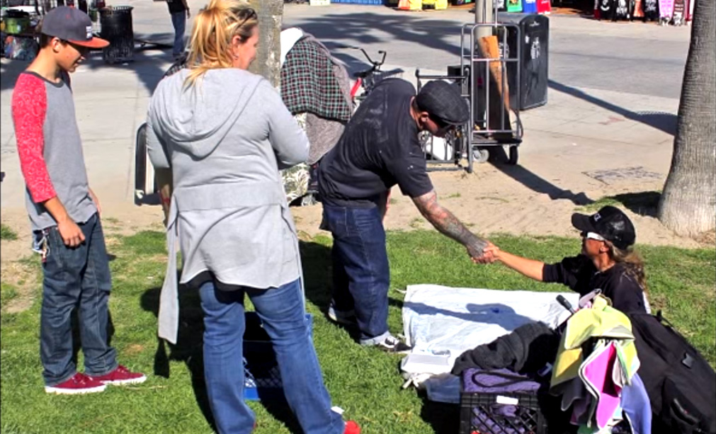 3 Gobble Gobble Give Volunteers give food to homeless man